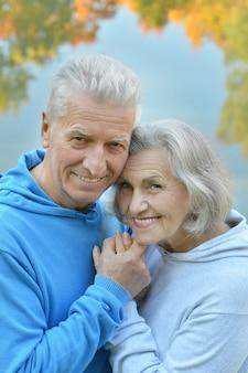 Glückliches älteres paar in der nähe von fluss im herbst, unscharfer hintergrund