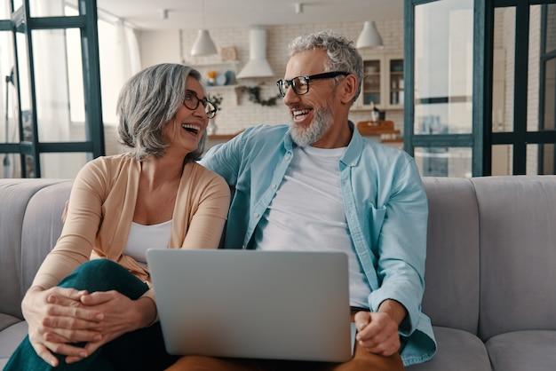 Glückliches älteres paar in freizeitkleidung, das lächelt und laptop benutzt, während es zu hause zusammenhält?