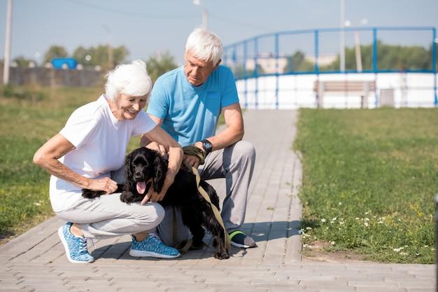 Glückliches älteres paar mit haustier-hund