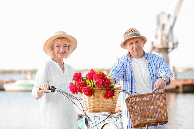 Glückliches älteres paar mit ihren fahrrädern nahe fluss