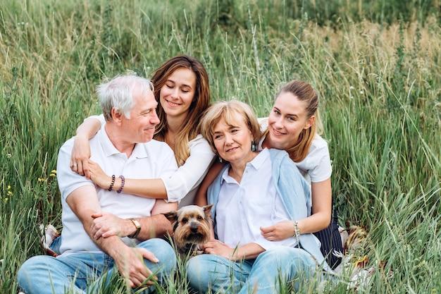 Glückliches älteres paar mit ihren töchtern in der natur