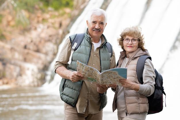 Glückliches älteres paar mit rucksäcken und karte, die vor kamera mit wasserfällen hinten stehen, während reise genießen