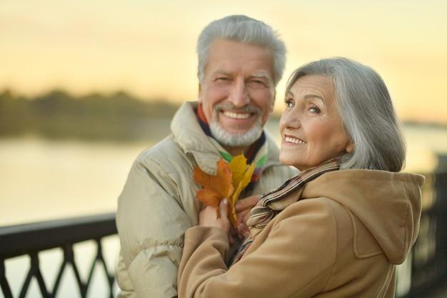 Glückliches älteres paar nahe fluss im herbst