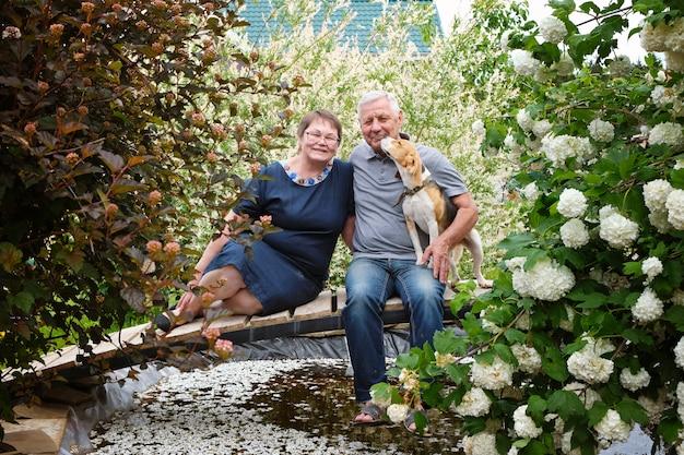 Glückliches älteres paar - reifer mann und frau an ihrem haus mit hundehaustier