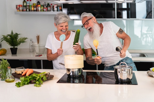 Glückliches älteres paar tanzt beim gemeinsamen kochen zu hause