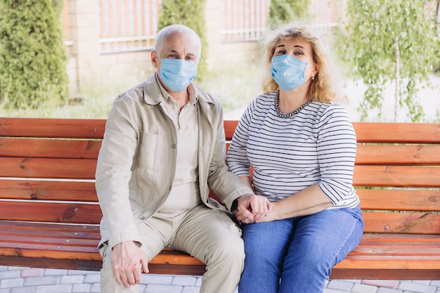 Glückliches älteres seniorenpaar, das medizinische maske trägt, um vor coronavirus im sommerpark zu schützen