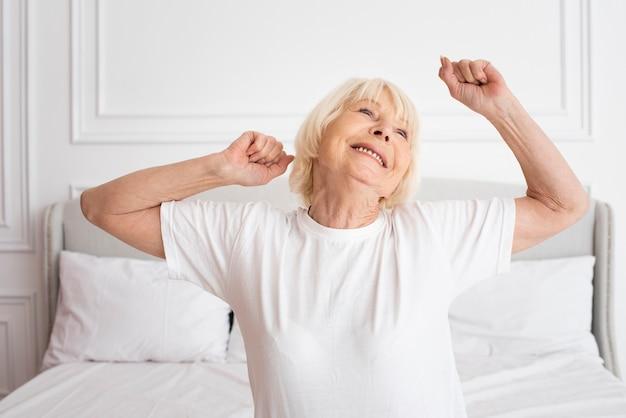 Glückliches älteres sitzen im schlafzimmer