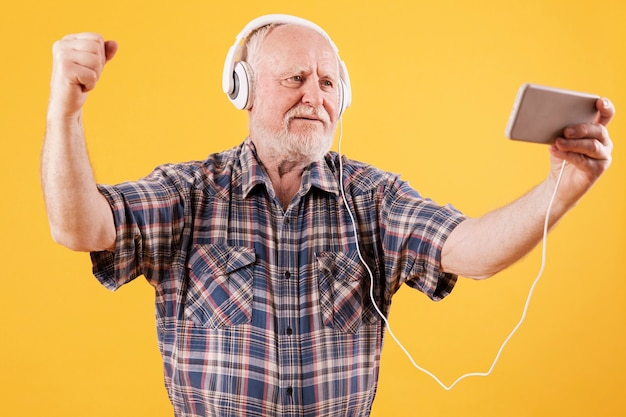 Glückliches älteres tanzen und aufpassende videomusik