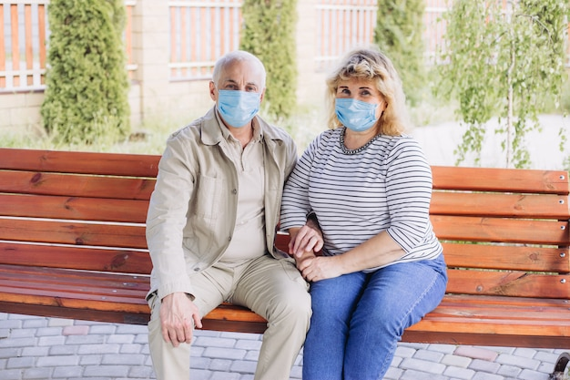 Glückliches älteres verliebtes paar, das medizinische maske trägt, um vor coronavirus zu schützen. im freien parken, coronavirus-quarantäne