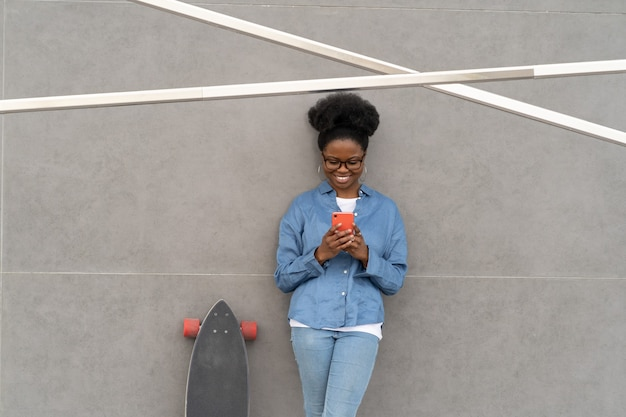 Glückliches afrikanisches mädchen in hipster-brille liest nachricht im smartphone oder chattet mit einem freund, der das internet nutzt