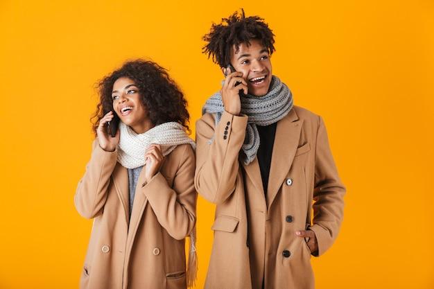 Glückliches afrikanisches paar, das winterkleidung trägt, die isoliert steht und auf handy spricht