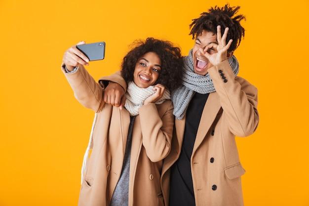 Glückliches afrikanisches paar, das winterkleidung trägt, die isoliert steht und ein selfie nimmt