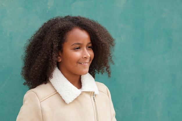 Glückliches afroamerikanermädchen mit dem afrohaar auf einem grünen hintergrund