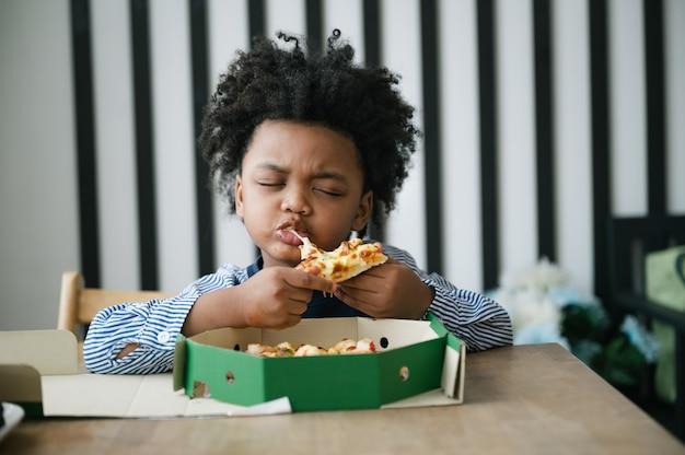 Glückliches afroamerikanisches kind, das pizza auf dem tisch isst