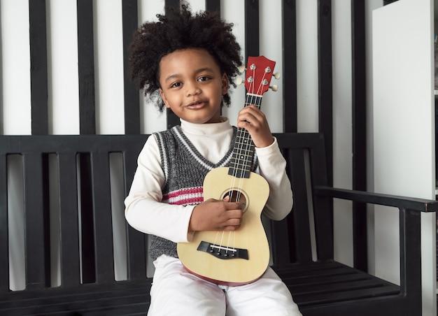 Glückliches afroamerikanisches kind hält ukulele und schaut mit einem lächeln in die kamera
