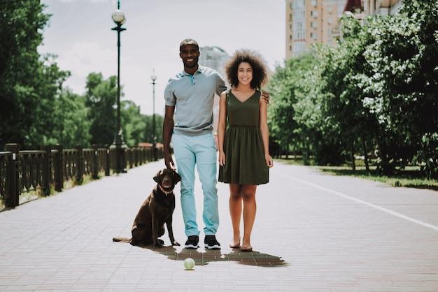 Glückliches afroamerikanisches paar, das mit hund geht