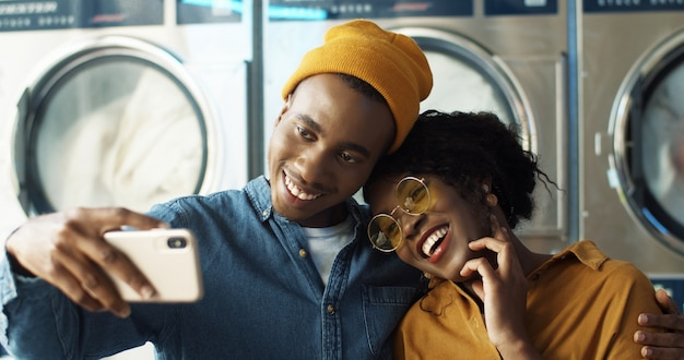 Glückliches afroamerikanisches paar in der umarmung und im lächeln zur smartphone-kamera beim selfie-foto im wäscheservice. fröhlicher junger mann und frau, die fotos am telefon an waschmaschinen machen.