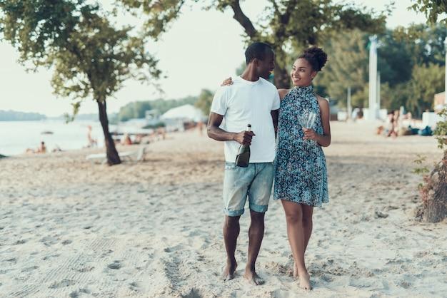 Glückliches afroamerikanisches paar steht auf sandy river beach still.