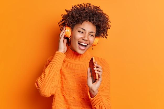 Glückliches afroamerikanisches weibliches modell singt lied hält smartphone nahe mund, als ob mikrofon drahtlose kopfhörer auf ohren trägt, lächelt breit isoliert über lebendige orange wand