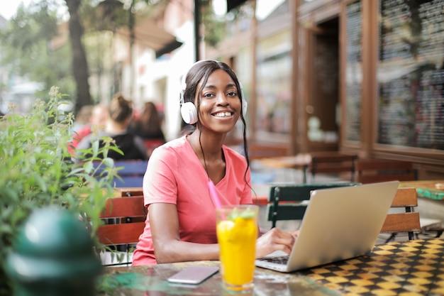 Glückliches afromädchen, das auf einer terrasse sitzt