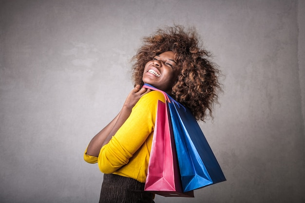 Glückliches afromädchen mit einkaufstaschen
