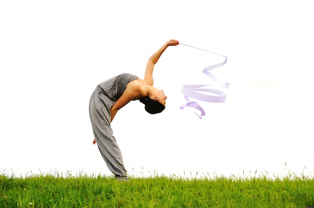Glückliches akrobatisches mädchen auf wiese
