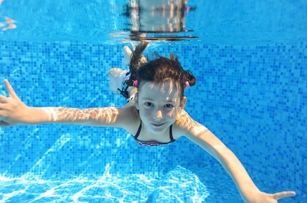 Glückliches aktives kind schwimmt unter wasser im pool