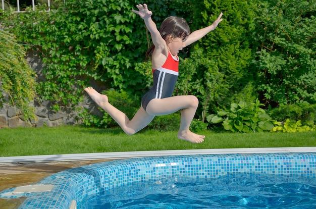 Glückliches aktives kind springt zum swimmingpool. schönes lächelndes mädchen, das spaß auf sommerferien hat. kindersport und urlaub
