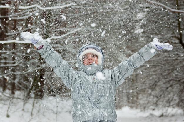 Glückliches aktives mädchen, das spaß hat und schnee im winterwald, lächelndes spielendes kind wirft. kind im winterurlaub