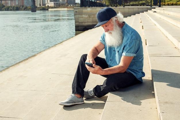 Glückliches alter. der grauhaarige alte mann, der rentner, benutzt ein telefon mit einem lächeln