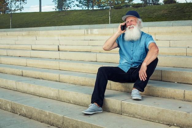 Glückliches alter. grauhaariger alter mann mit einem lächeln am telefon