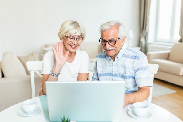 Glückliches altes familienpaar, das mit freunden und familie unter verwendung des laptops spricht