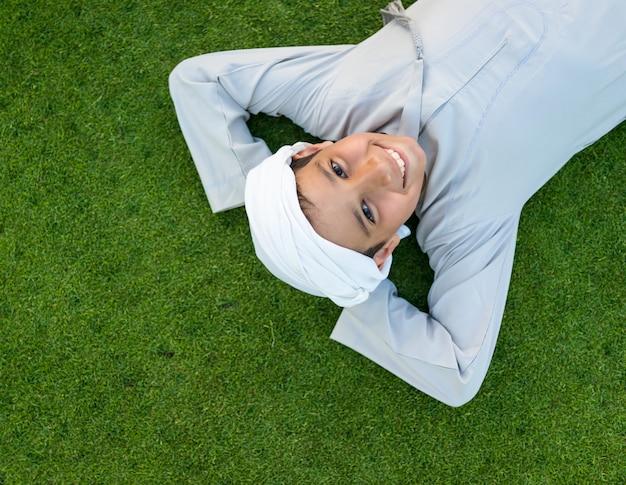 Glückliches arabisches kind auf grünem gras