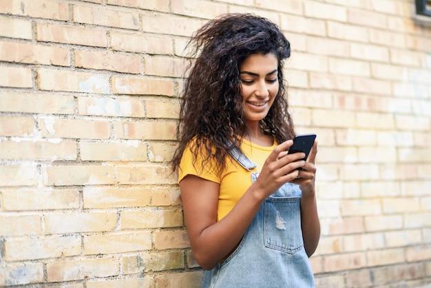 Glückliches arabisches mädchen, das intelligentes telefon auf backsteinmauer verwendet.