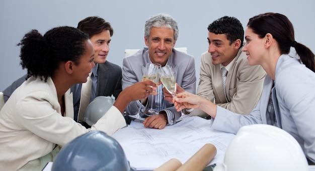 Glückliches architectutal team, das eine feier mit champagner hat
