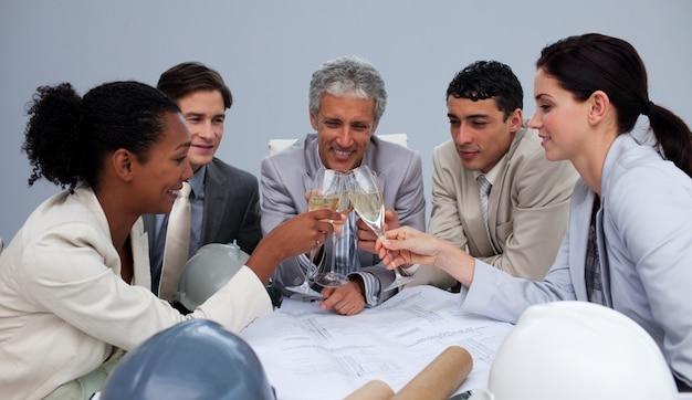 Glückliches architectutal team, das einen erfolg mit champagner feiert