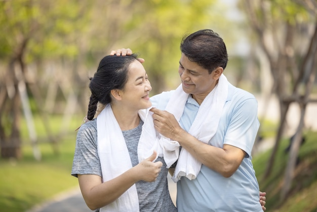 Glückliches asiatisches älteres paar, das draußen im park joggt.