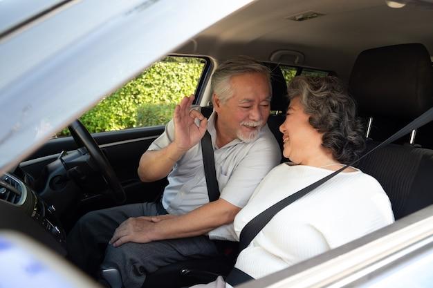 Glückliches asiatisches älteres paar, das im auto sitzt und auto auf reise fährt.