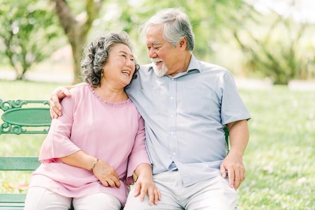 Glückliches asiatisches älteres paar, das lacht und lächelt, während es im park sitzt