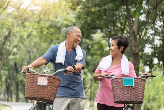 Glückliches asiatisches älteres paar im blauen und rosa hemd lachend, während die fahrräder reiten.