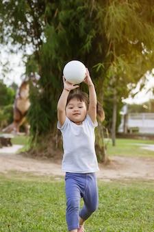 Glückliches asiatisches baby, das läuft oder springt und am park- oder gartenfeld spielt sie lächelt und lacht