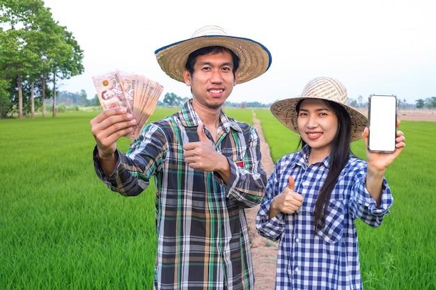 Glückliches asiatisches bauernpaar, das thailändische banknote und smartphone mit leerem bildschirm an reisfarm hält