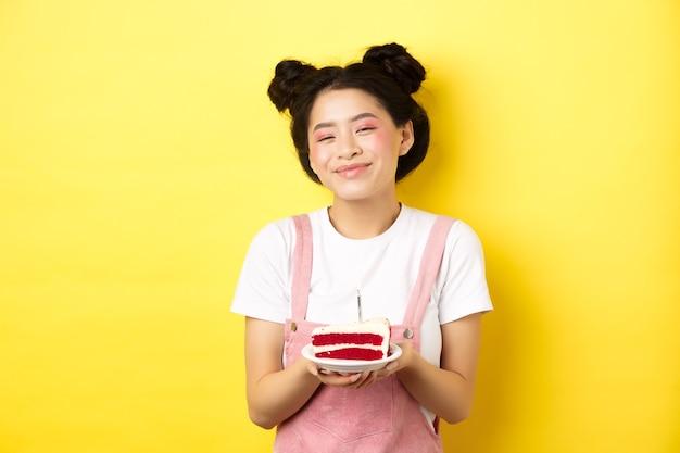 Glückliches asiatisches geburtstagskind mit hellem make-up, kerze auf kuchen blasend, wunsch machend, auf gelb stehend.