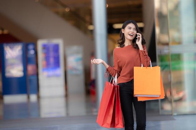 ็ glückliches asiatisches hübsches mädchen, das einkaufstaschen bei der anwendung des smartphone hält