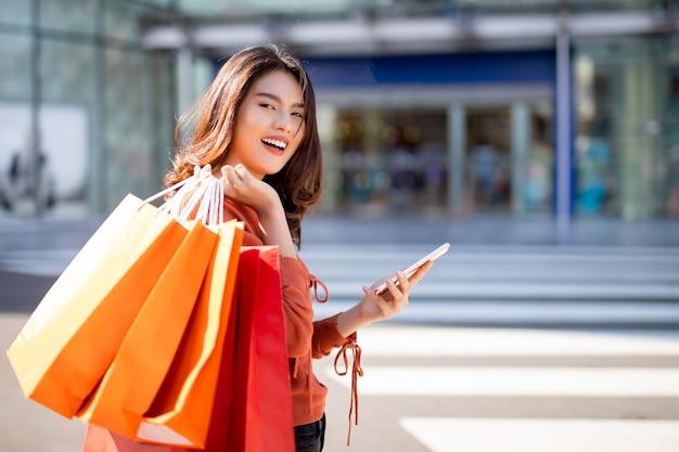 Glückliches asiatisches hübsches mädchen, das einkaufstaschen bei der anwendung des smartphone hält
