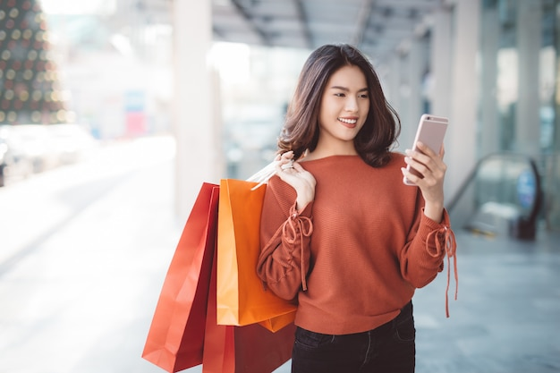 Glückliches asiatisches hübsches mädchen, das einkaufstaschen beim betrachten des intelligenten telefons hält