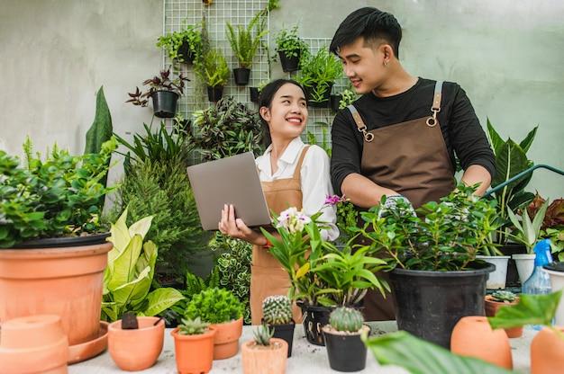 Glückliches asiatisches junges gärtnerpaar, das schürze trägt, verwendet gartengeräte und laptop-computer, um sich zu kümmern