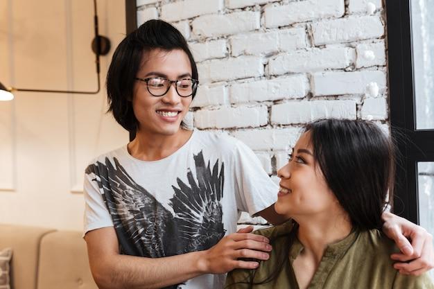 Glückliches asiatisches junges liebendes paar, das im café sitzt