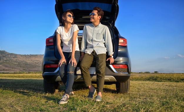 Glückliches asiatisches junges paar auf einem roadtrip. asiatisches paar mann und frau, die auf der rückseite des autos sitzen, reisen zu berg und see im urlaub mit autostraße