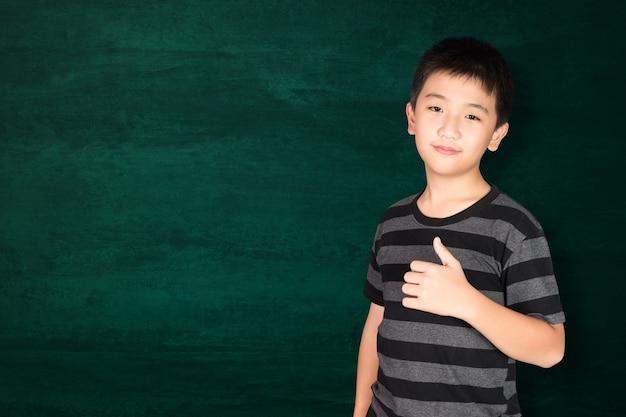 Glückliches asiatisches kind, das auf leerer grüner tafel lächelt